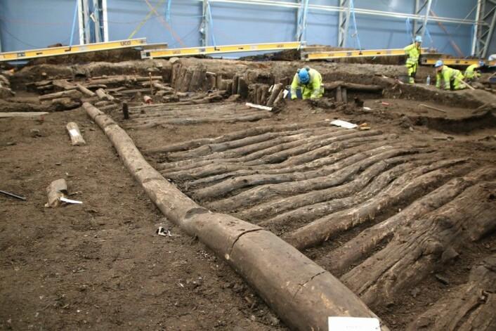 Figur 5: Stokkedekke i Bispeallmenningen gravd ut i 2018. Dette nivået ligger under bolverket som kan sees på figur 2, og kan dateres til 1200- eller 1300-tallet. Bildet er orientert mot sør. Foto: Thomas Wrigglesworth, NIKU.