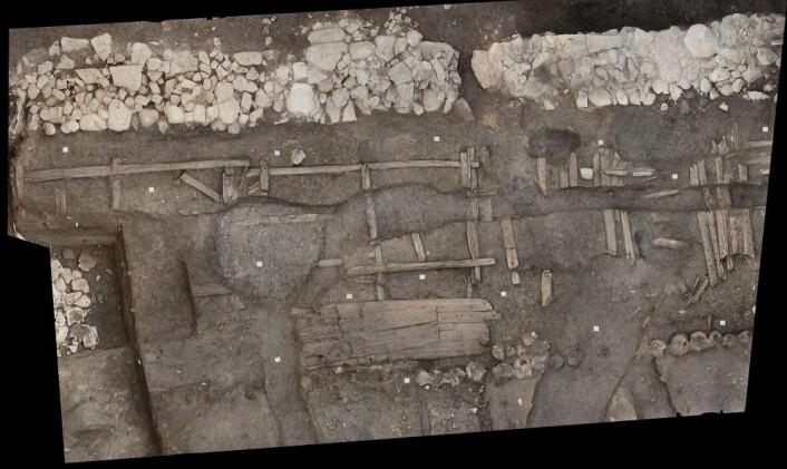 Figur 2: Et nivå av Bispeallmenningen gravd ut i 2018, vest for den delen av allmenningen som ble gravd ut i 1953–54. Bolverket ser ovenfra ut som kvadrater satt sammen av trestokker. På bildet kan man også se de gjenbrukte båtdelene i gatens søndre veiskulder. Bildet er omtrentlig orientert mot nord. Fotogrammetri: Adam Hultberg og Joachim Åkerstrøm, NIKU.