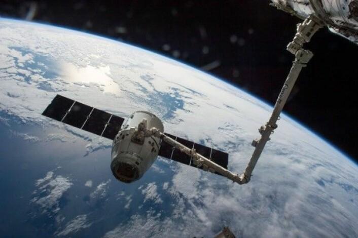 Dragon-forsyningsfartøy fanget inn av romstasjonens robotarm. NASA