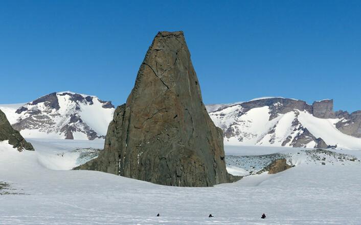Storsponen i Hochlinfjella, finslipt av isen til en spiss nunatakk, består av smeltebergarten monzonitt. I nedre kant tre snøskutere på vei til fjellet. (Foto: Ane K. Engvik)