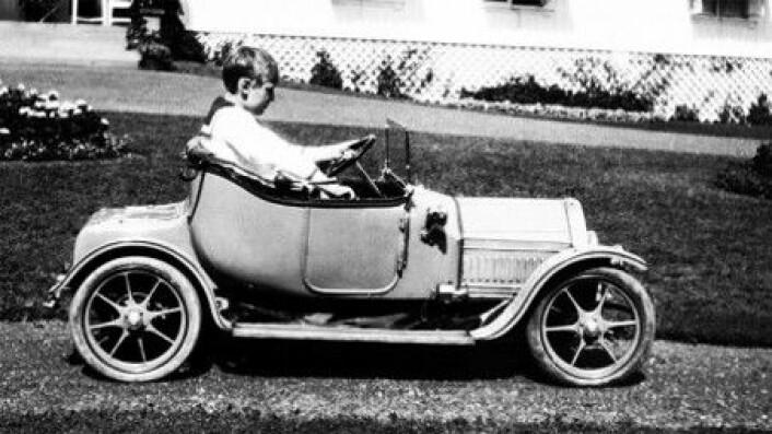 Kong Olav fikk bil allerede som liten gutt. Ikke hvilken som helst bil heller. Dette er nemlig en tro og avansert kopi av en ordentlig Cadillac fra 1912, men med elektrisk motor.Det ble bygget tre slike biler. Kong Olavs var en julegave fra mormor, dronning Alexandra av Storbritannia, i 1912. Den andre fikk prinsen av Siam og den siste bilen fikk barnebarnet til Cadillacs grunnlegger, Wilfred Leland Jr.Det sies at Kong Olav flittig brukte den lille bilen på Bygdøy kongsgårds mange grusganger. (Foto: A.B. Wilse/Det kongelige hoffs fotoarkiv)
