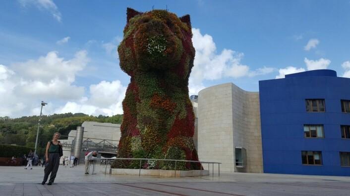 """Det eneste turistaktige bildet jeg har fra Bilbao, men også det med botanisk tema. Her er jeg foran den berømte skulpturen """"Puppy"""" av Jeff Koons, som er laget i rustfritt står, jord og blomstrende planter. Foto: Tilfeldig turist"""