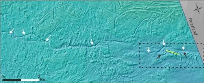 Midt i Barentshavet kan man se elvekanaler (hvite piler) langs havbunnen på omtrent 250 meters dyp. Disse er dannet av smeltevann, under en tidligere isbre. Svarte piler peker på en esker, bestående av sand, grus, stein og blokk avsatt i en tunnel under isen før den smeltet. Gul linje viser et videotransekt over eskeren. Striplet firkant viser inzoomet bilde av ekseren og elvekanalen. Foto: Mareano