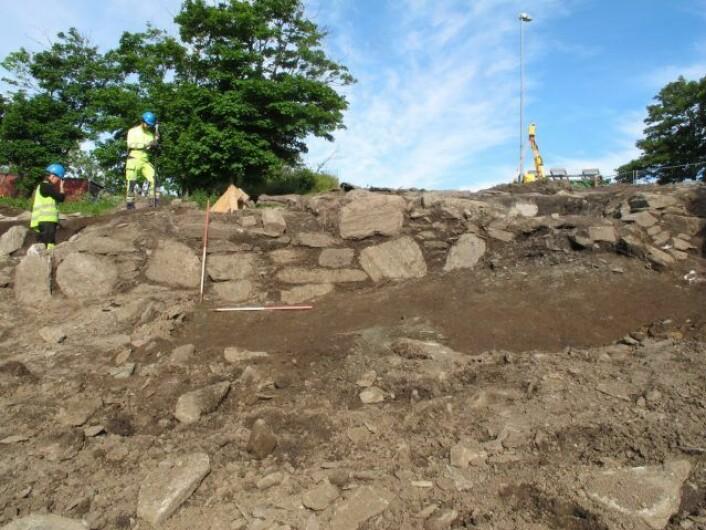 Utgravningsleder Erlend Nordli og feltleder Anette Sand-Eriksen er i gang å fjerne den ene jordbenken som sto igjen inne i ruinen etter utgravningen i 2012. I forgrunnen kan man se østmuren som vender ned mot havnområdet. (Foto: Frida Espolin Norstein, UiO)