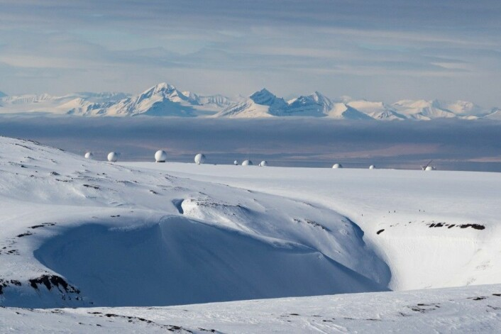 Svalbard i mai 2017; Menneskene nede på Platåfjellet blir ubetydelig i en mektig natur, mens satellittstasjonen ruver i Svalbards internasjonale rolle. (Foto: Børge Damsgård)