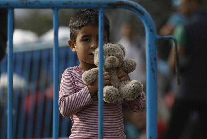 En syrisk gutt holder bamsen sin mens han venter bak politibarrierene ved grensen mellom Hellas og Makedonia. (Foto: NTB scanpix)