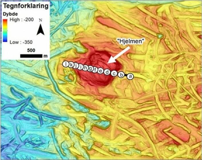 Skyggerelieff av havbunnen basert på terrengmodell med oppløsning 5 m mellom dybdepunktene. Den hvite pilen peker på Hjelmen, der vanndypet er ca. 165–210 meter. Furene på havbunn er isfjellpløyespor. De hvite sirklene merket a–l ligger langs transektet, og viser plassering av bildene a-l nedenfor. (Foto: MAREANO)