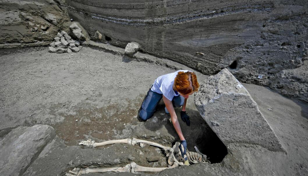 Arkeolog Valeria Amoretti børster forsiktig bort sand fra et skjelett de nylig fant ved Pompeii.  (Foto: AP)