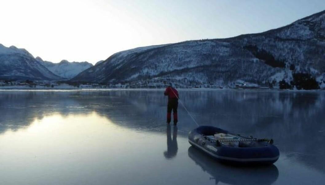 Chris Petrich drar gummibåten ut til bøya i Beisfjord for å laste ned målinger fra sonden samt samle isprøver. (Foto: Megan O'Sadnick)