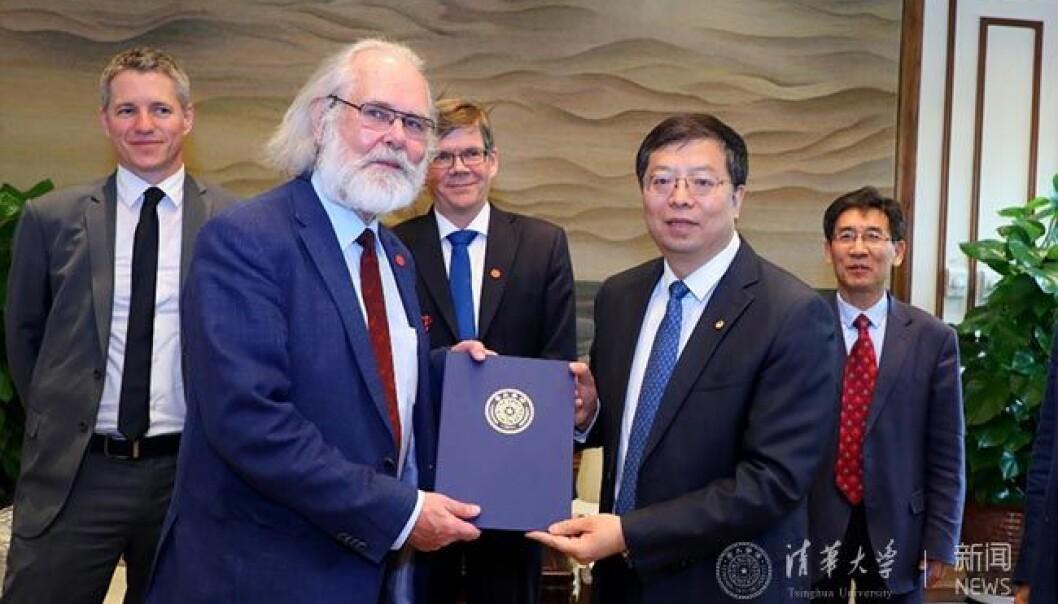 Nils Chr. Stenseth mottar beviset på sitt æresdoktorat av Qui Yong.  (Foto: Tsinghua-universitetet)