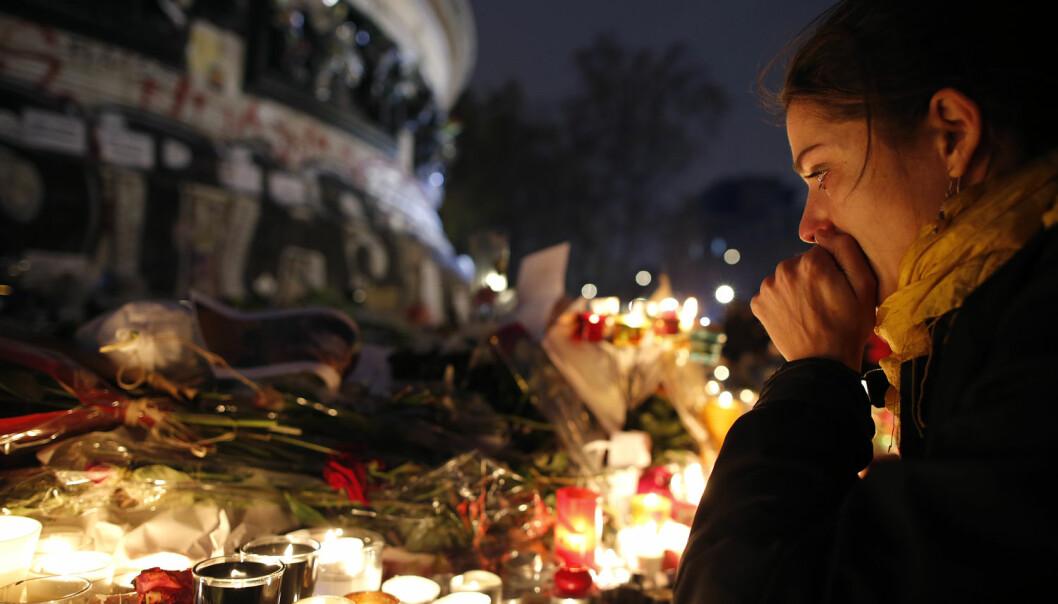 En kvinne ved et minnested for ofrene etter terrorangrepene i Paris 13. november 2015. De seks angrepene tok livet av til sammen 130 mennesker. (Foto: Christian Hartmann/Reuters/NTB scanpix)
