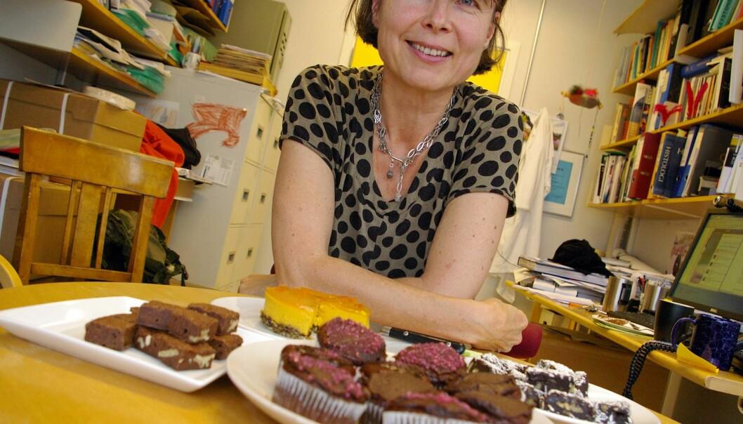 Anne Spurkland med kontoret fullt av kaker. Her ser du muffins uten egg og melk, brownies uten mel og melk, brownies med svisker, uten sukker, egg, melk og mel, og i bakgrunnen skimtes en ostekake uten noen av disse ingrediensene. (Foto: Bjørnar Kjensli)