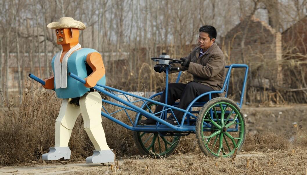 Blir man født kreativ? Her viser den kinesiske oppfinneren og bonden Wu Yulu fram roboten sin. Han har bygget roboter siden åttitallet og alle sammen er laget av ting han har funnet på søppelhauger. (Foto: Reinhard Krause, reuters, NTB scanpix)