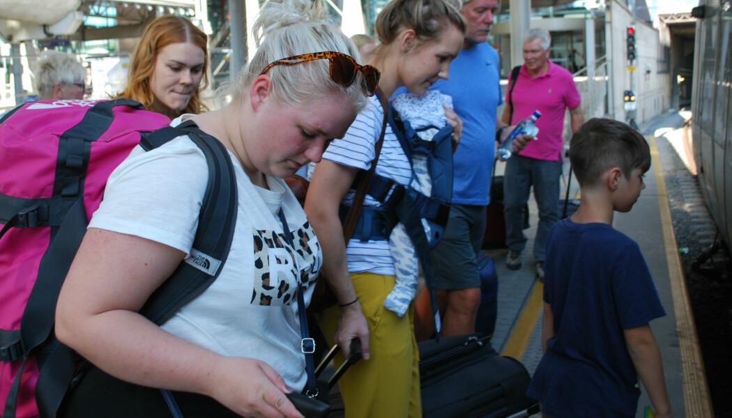 Det var mange som skulle til Gardermoen søndag formiddag midt i fellesferien. Kamilla, Silje og Iselin gjør seg klare til å gå ombord i flytoget. (Foto: Marte Dæhlen, forskning.no)
