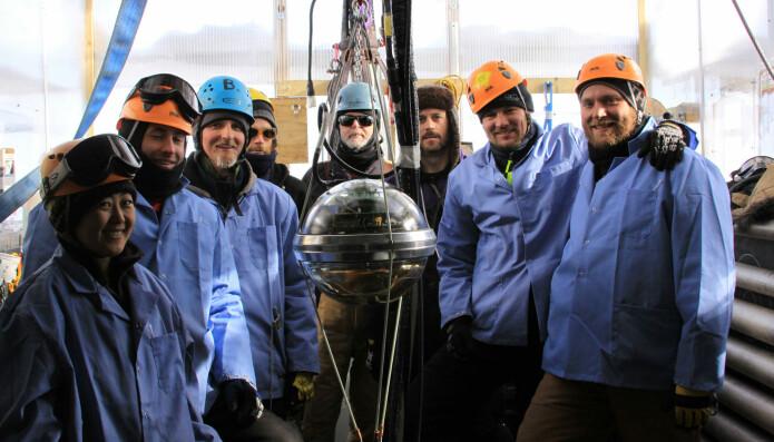 En del av teamet bak IceCube-prosjektet foran en av sensorene som skal ned i isen. Det er over 5000 av sensorene der nede. (Bilde: AFP PHOTO / HO / NSF / F. DECAMPS/NTB Scanpix)