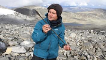 En arkeolog holder en ca. 1400 år gammel pil, som gikk tapt i forbindelse med reinsjakt i høyfjellet i Oppland under the Late Antique Little Ice Age.  (Foto: Julian Martinsen, secretsoftheice.com/Oppland fylkeskommune)