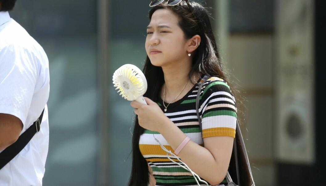 En kvinne i Tokyo forsøker å kjøle seg ned med en håndholdt vifte under hetebølgen. Mandag ble det satt ny varmerekord i Japan med 41,1 grader. (Foto: Koji Sasahara, AP Photo, NTB scanpix)