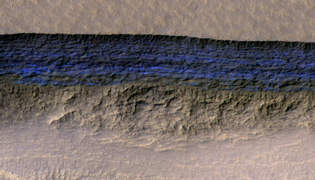 Bildet viser et rundt 500 meter langt stykke av en av skrentene som ble undersøkt. Fargene i lyset vitner om at den nesten 130 meter høye veggen består av frossent vann.  (Foto:  NASA/JPL-Caltech/UA/USGS)