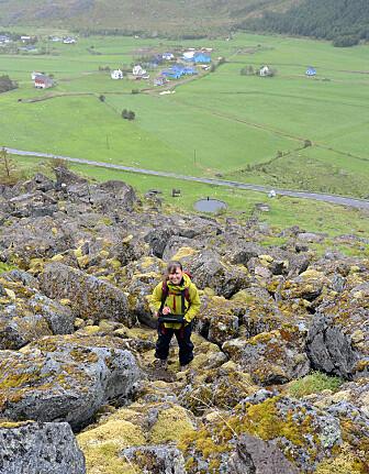 Forsker Kari Sletten står i ei steinur under Guratinden i Sennesvik i Lofoten. Her kartlegger hun alt hun ser i skråningen og undersøker blant annet gamle skredbaner. (Foto: NGU)
