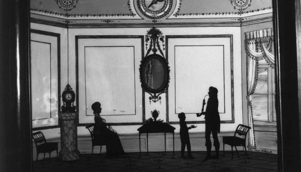 Familiebilde: Noen silhuetter ble også lagt oppå tegnede bakgrunner. Slik fikk man vist også familiens stue og hjem (Eier: Norsk folkemuseum)