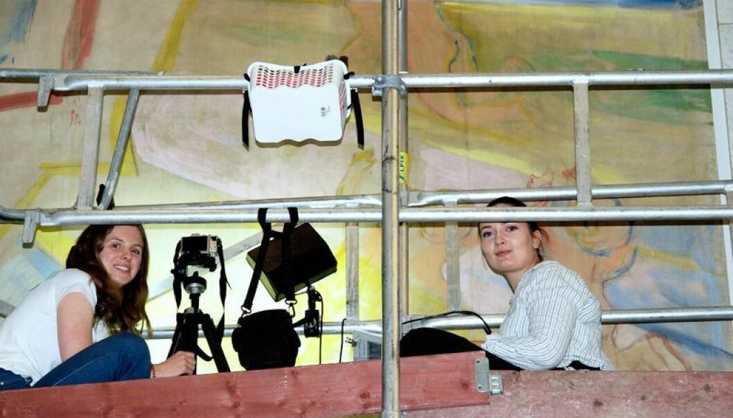Masterstudent Marte Løvseth og bachelostudent Stephanie Frenz fjernar sot og overflatestøv frå Munch-måleriet Genier i lysflommen i Universitetets aula. (Foto: Martin Toft)