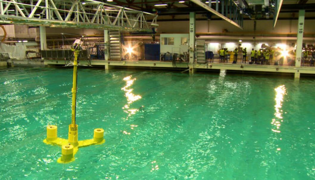 En liten modell av den flytende vindmøllen har blitt testet under forskjellige værforhold i forskningsbassenget til SINTEF Ocean. Istedenfor å lage en nedskalert rotor til havvindmøllen har forskerne testet forskjellige vindstyrker ved hjelp av blant annet wire festet til modellen. (Foto: SINTEF)