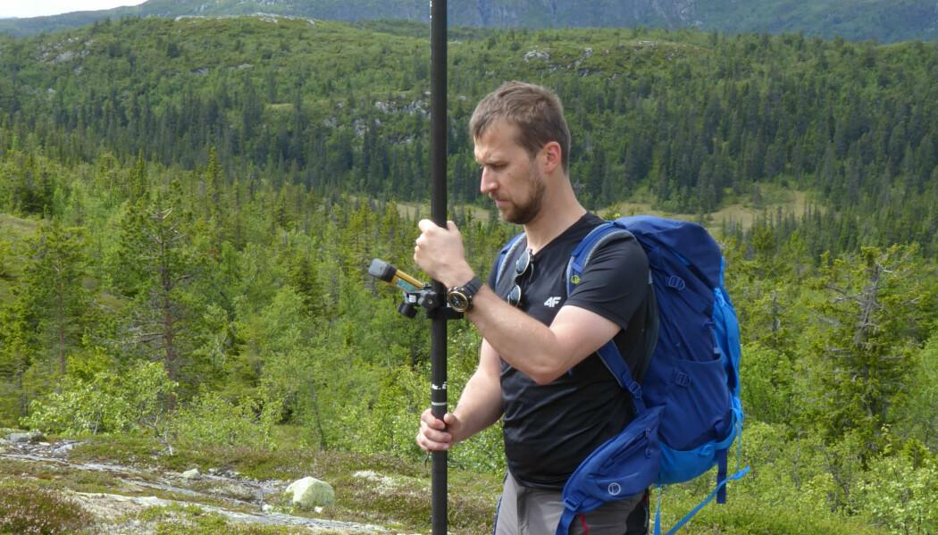 Her foretar forsker Marek Pierzchala innmåling av koordinater for et bakkekontrollpunkt før flyvning med drone og digitalt kamera nær tregrensen i Rollag kommune i 2017. (Foto: NMBU)