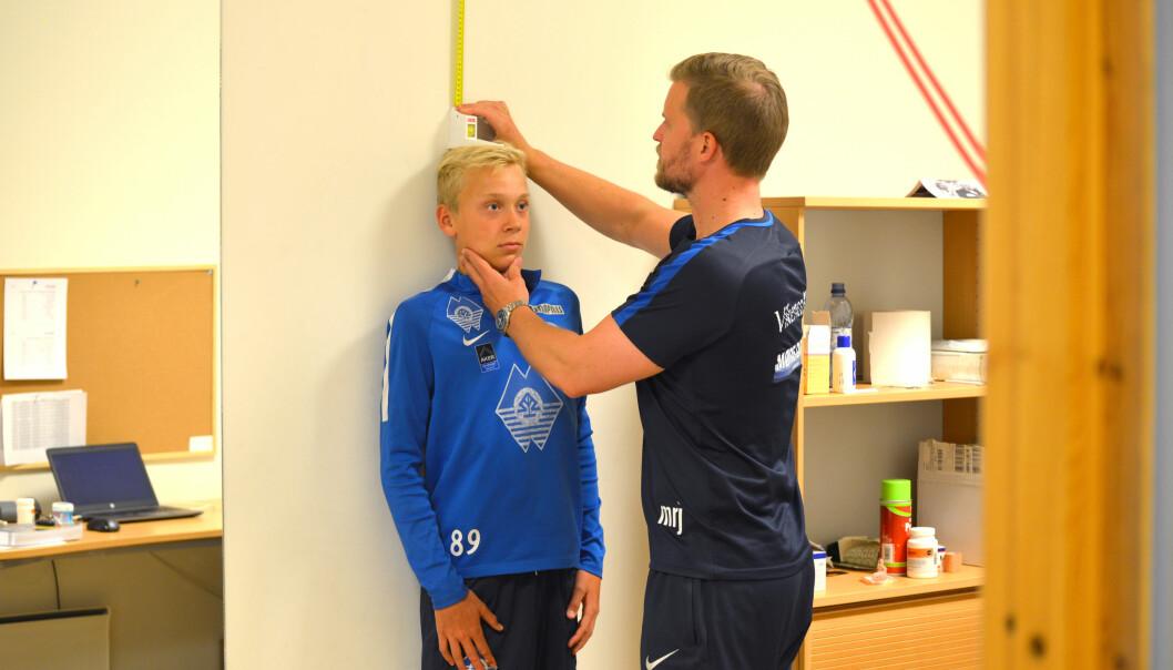 Manuellterapeut Mats Jørgensen måler hvor mye Nikolai Skuseth har vokst siden sist. Dersom det er 0,6 centimeter eller mer, må fotballklubben vurdere om de skal tilpasse treningsmengden hans, slik at de unngår skader. (Foto: Hilde R. Johnsen)
