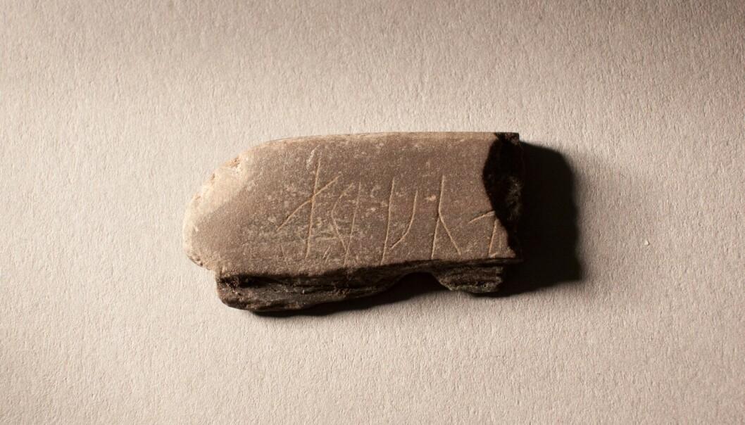 Bryne med runeinnskrift ble funnet i det som var middelalderbyen i Oslo, rett vest for Bispeborgen. Oversiden har fem tydelige runer, der den siste er brukket av, og rune to er litt svakere enn de andre.  (Foto: Karen Langsholt Holmqvist / NIKU)