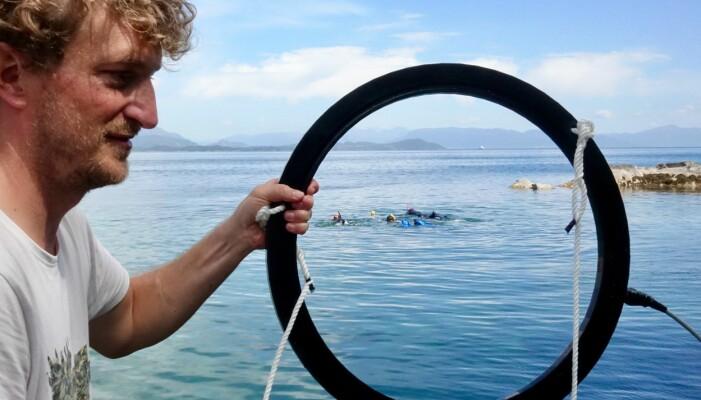 Daniel Nyqvist held opp ein ring som skal ligge rundt eit grøngyltereir. På ringen festar ein antenner, kamera og mikrofon, og informasjonen som blir sanka inn skal seinare koplast mot avanserte algoritmar. (Foto: Torhild Dahl, Havforskningsinstituttet)