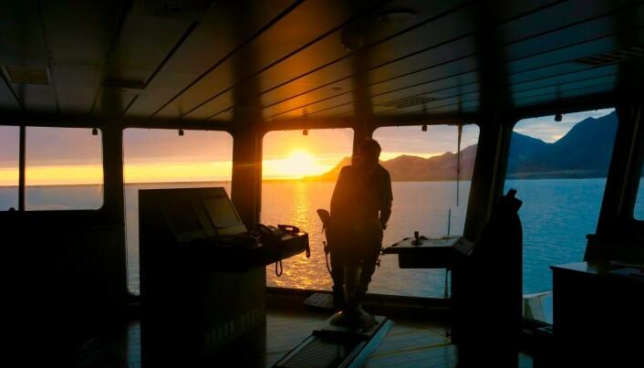 Overstyrmannen på G.O. Sars og midnattssola hengende over den blikkstille Kongsfjorden. (Foto: Frida Eriksdatter Tradin)