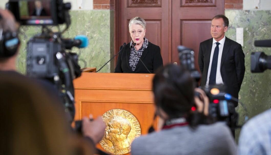 Berit Reiss-Andersen, leder av Nobelkomiteen, og komiteens sekretær Olav Njølstad (i bakgrunnen), offentliggjør Den internasjonale kampanjen for forbud mot atomvåpen, ICAN som vinner av årets fredspris på Nobelinstituttet i Oslo fredag.  (Foto: Heiko Junge / NTB scanpix)