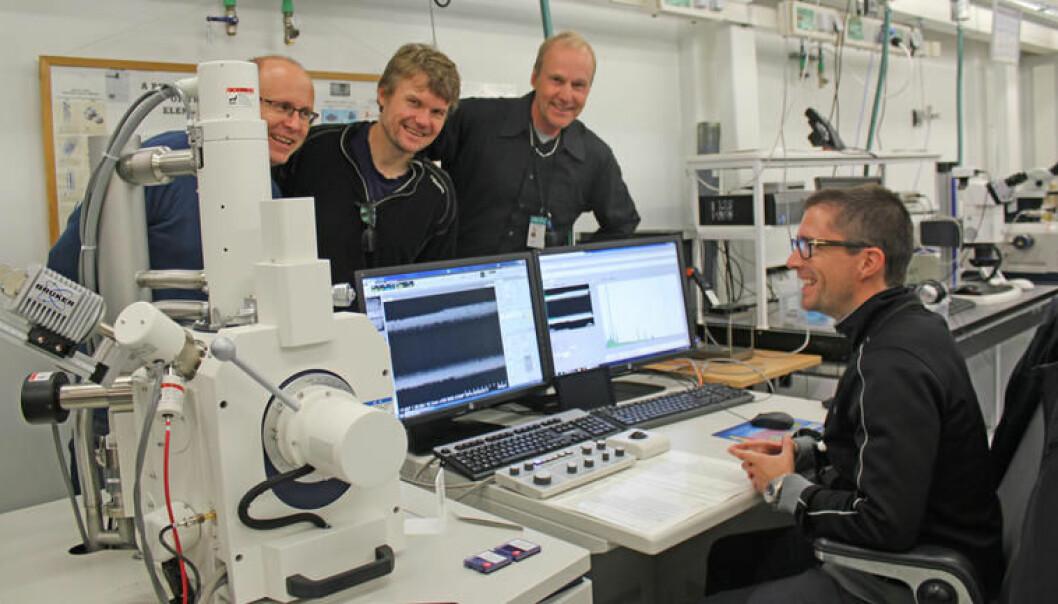 Bakerst til venstre er stipendiat Rune Langøy, teamleder for CERN-gruppa i HSN Jørgen Lien og laboratorieleder Ole Henrik Gusland samlet rundt elektronmikroskopet som opereres av stipendiat Lars Holhjem. Det forstørrer opptil en million ganger. (Foto: Per Magnus Holtung)