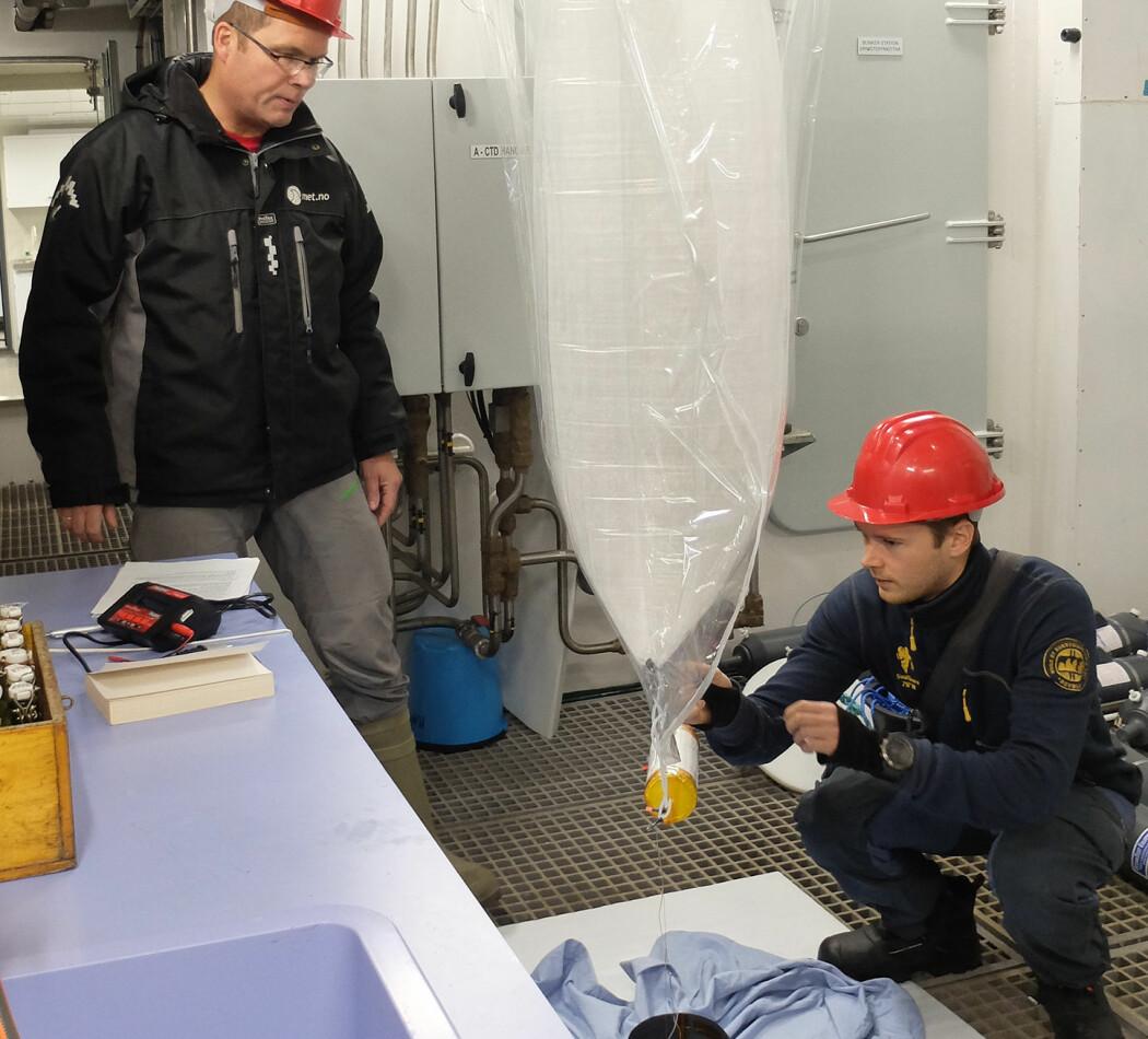 Lars Hole (til venstre) og Jean Rabault har fylt ballongen og sjekker at instrumentet og solcellepanelet fungerer som det skal. (Foto: Inger Lise Næss/UNIS)