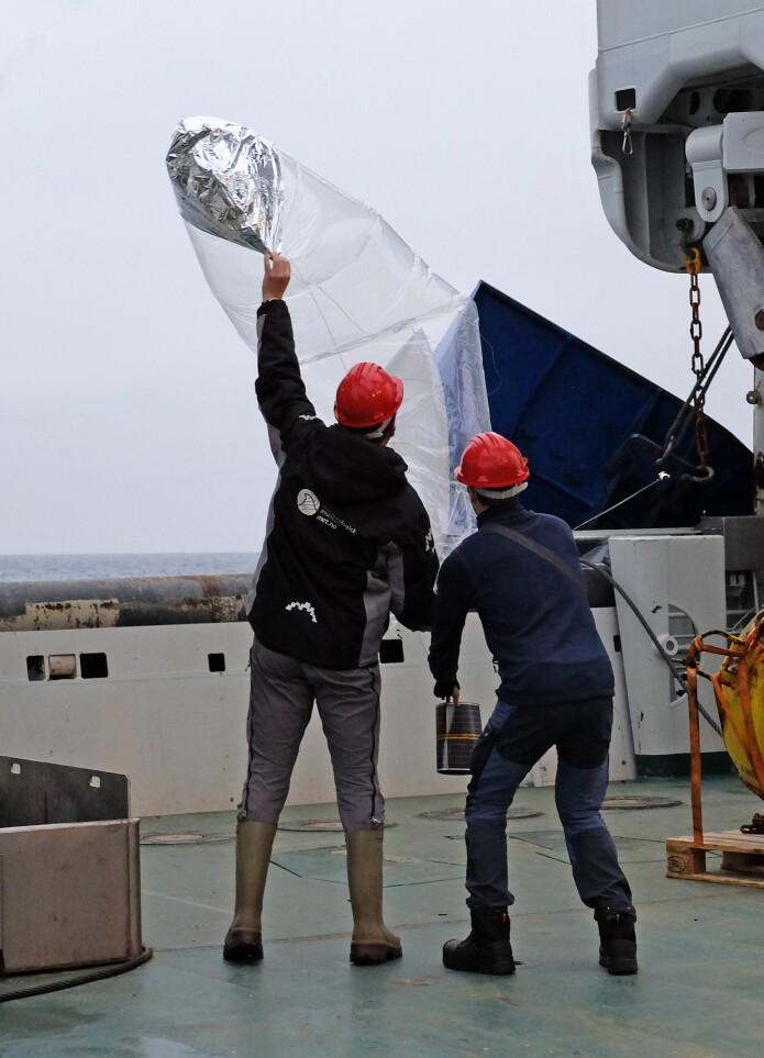 Ballongen slippes forsiktig akterut på båten. (Foto: Inger Lise Næss/UNIS)