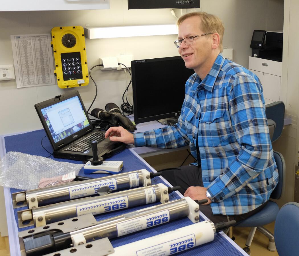 Frank Nilsen laster inn dataene fra temperaturloggerne. På bordet ligger målerne for saltholdighet, temperatur og trykk. (Foto: Inger Lise Næss / UNIS)