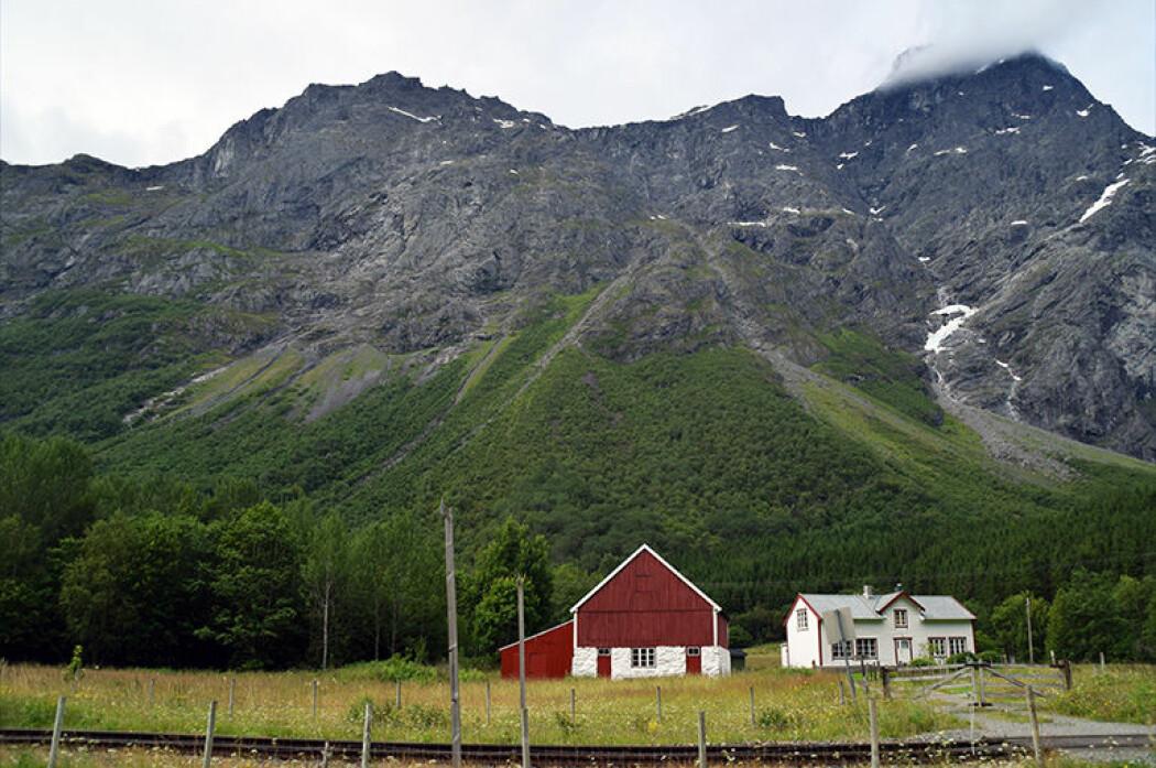 Mannen troner høyt over Romsdalen, hele 1294 meter over havet. Lengst oppe, hvor skredene utløses, er det stupbratt. Under ligger skredmassene som nå er datert. I forgrunnen ligger skinnegangen til Raumabanen. (Foto: NGU)