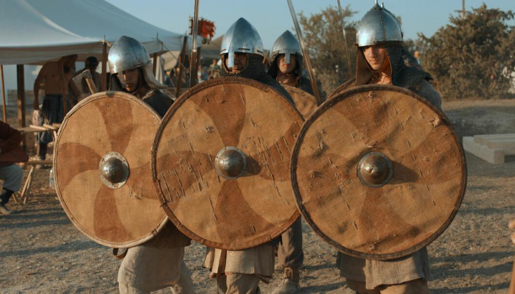 Når vikingene gikk til kamp, forestiller man seg i dag, dannet de lange skjoldmurene av overlappende skjold, som ofte etterlignes av såkalte reenactment-grupper. Men da ville skjoldene blitt maltraktert av fienden, mener arkeolog.  (Foto: LVStock / Shutterstock / NTB scanpix)