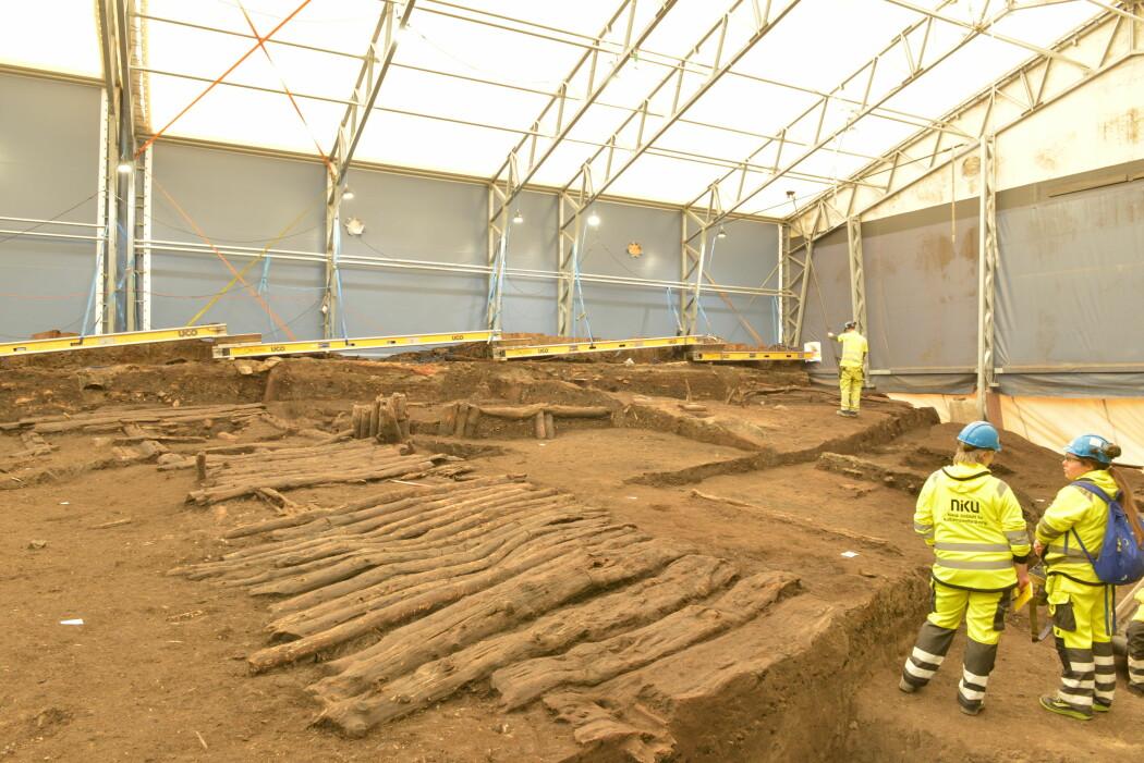De arkeologiske utgravingene i Follobaneprosjektet gikk over flere år og i forskjellige etapper. Våre forsøk var knyttet til to av disse etappene. Oversiktsbilde av et av utgravingsfeltene der trebroleggingen fra middelalderens Bispegata er i forgrunnen. Vårt skanningsobjekt, som var den andre av to bygningskonstruksjoner som vi dokumenterte, vår bygning 2, ligger bakerst i feltet. (Foto: Erich Nau/ NIKU)