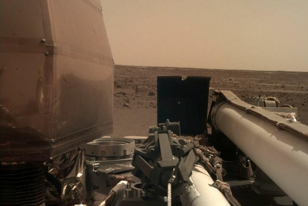 Et Insight-kamera med støvfilter skuer ut over et øde Mars-landskap. Her skal den jobbe i to år. (Foto: NASA/JPL-Caltech)