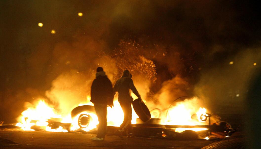 Ungdommer kaster bildekk på et bål av dekk og biltilhengere i bydelen Rosengård i Malmø. Bydelen har flere ganger vært åsted for sammenstøt mellom ungdom og politiet.  . (Foto: Drago Prvulovic / SCANPIX)