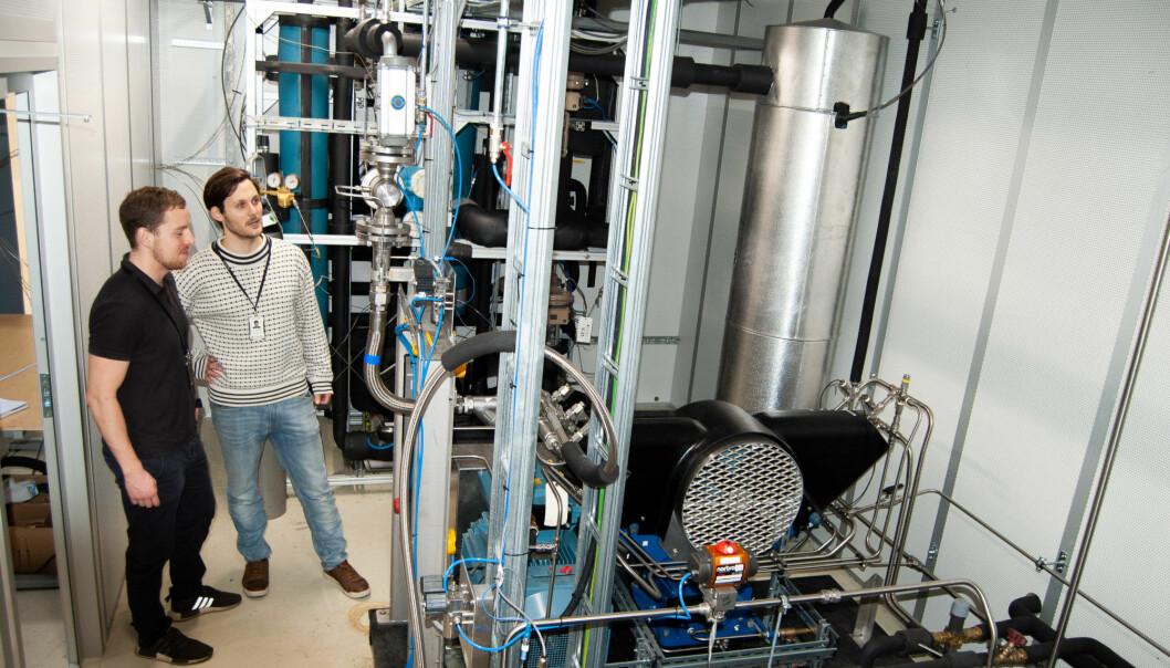 Målinger SINTEF-forskerne David Berstad og Stian Trædal (til venstre) har fått under forsøk med det nye systemet på denne lab-rigg i Trondheim viser at de ved å flytendegjøre CO2 oppnår en renhet på minst 99 prosent. (Foto: Håvard Egge)