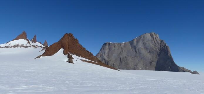 Fargeforskjellen i det lyse fjellet Hoggestabben og de brune pinaklene i Vedkosten reflekterer forskjellen mellom intrusjonsbergartene monzonitt og charnokitt (foto: Ane K. Engvik).