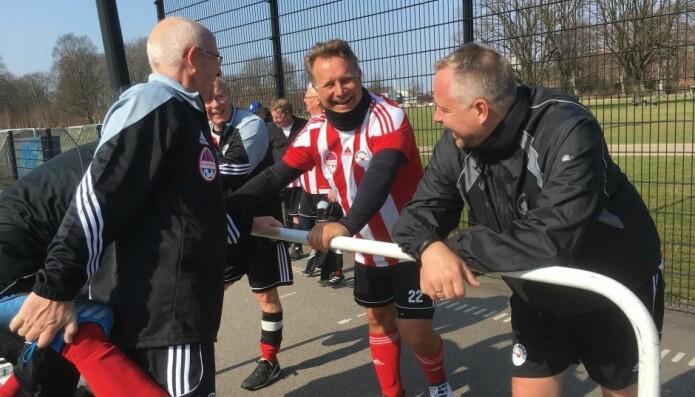 Spillerne får det bedre mentalt av å være en del av det fellesskapet som er på et fotballag, viser forskning. Her tøyer spillere ut på Østerbro i København. (Foto: DBU)