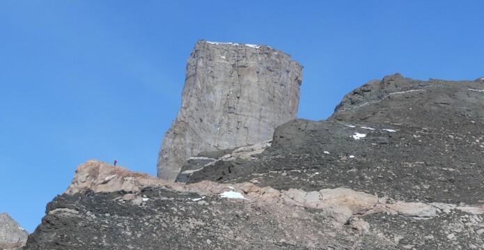 Geologene undersøker fjellklippen Stabben. Stabben har opphav som en intrusjon av den massive bergarten syenitt og ble stående igjen som en standhaftig klippe under senere tiders erosjon. Svart gabbro på fjellkammen foran blir kuttet av et rødt granittlag. (Foto: Ane K. Engvik)