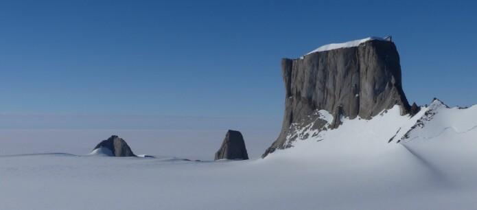 Det meste av Antarktis er dekket av is, men fjellene stikker opp som nunataker. Mange av de imponerende fjellene er dannet av store smeltebergarter størknet dypt i jordskorpen. Hoggestabben, med Småsponen og Storsponen til venstre, består av smeltebergarten monzonitt. (Foto: Ane K. Engvik)