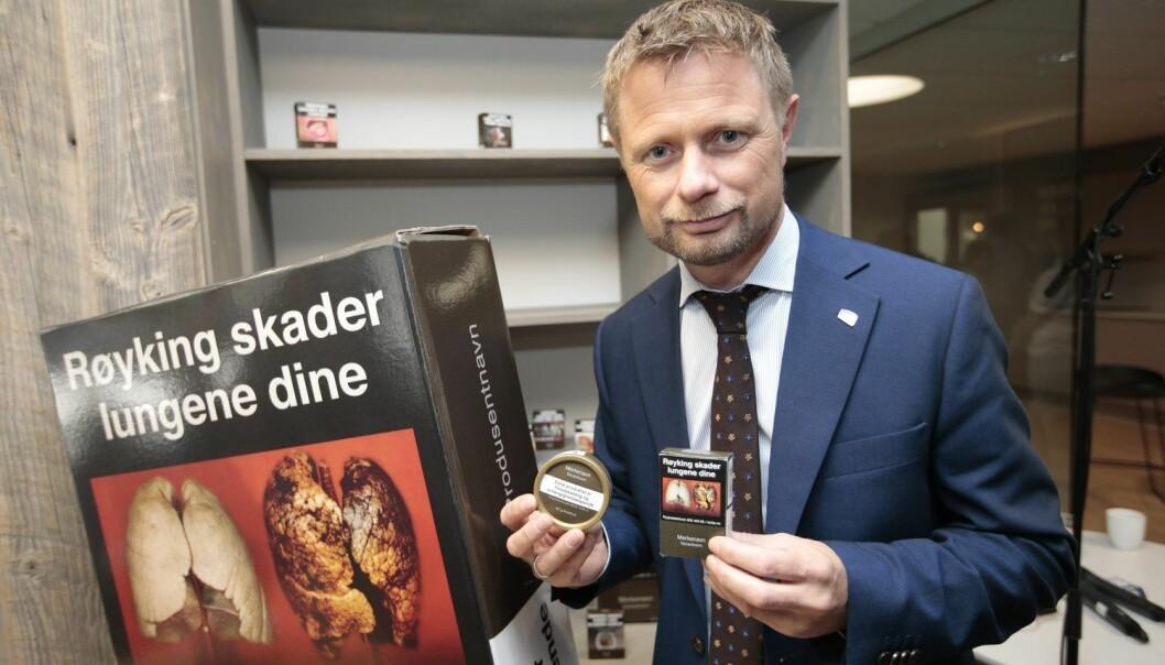 Helseminister Bent Høie viser fram de nye røykpakkene og snusboksene som kommer i butikken fra 1. juli i år. Han håper at det standardiserte utseendet på pakkene skal hindre at unge begynner å røyke eller snuse. (Foto: Lise Åserud/NTB scanpix)