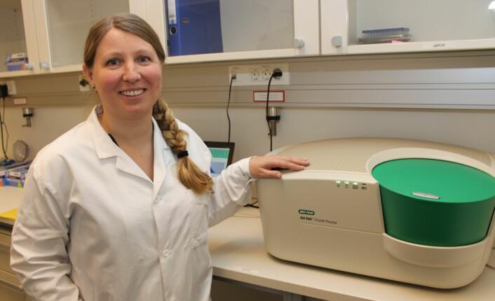 Professor Guro Lind med en digital PCR-maskin som blir brukt til å utvikle den nye urinprøve-baserte metoden for å påvise kreft i urinblæra. Maskinen er mye mer avansert enn det fotbad-liknende utseendet kan tyde på. (Foto: Bjarne Røsjø)