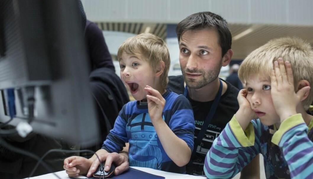 To unge hjelpere prøver spillet Quantum Shooter sammen med Jacob Sherson. Mandag får Sherson overrakt Forskningskommunikationsprisen 2017 i forbindelse med åpningen av Forskningens Døgn.  (Foto: Lars Kruse/AARHUS UNIVERSITET)