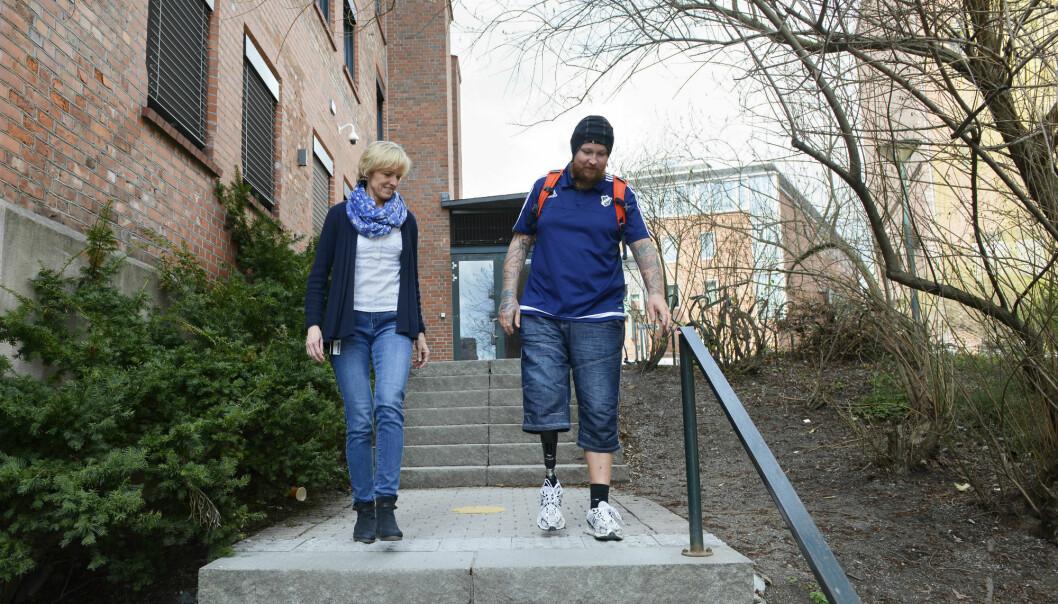 For å kartlegge hjerneaktivitet for benamputerte protesebrukere under gange, har deltakerne på seg en hette med sensorer som registrerer endringer i hjernens aktivitet. Her er Jette Schack sammen med Gunnar Westlund, som er en av deltakerne i prosjektet.  (Foto: Sonja Balci)